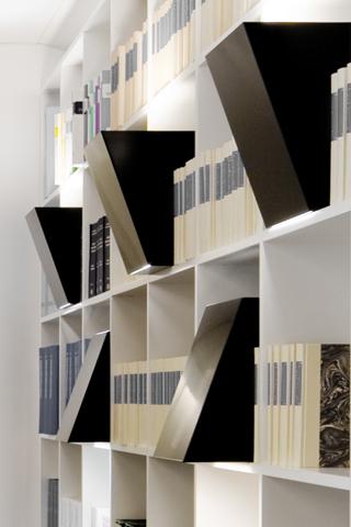 Die Regalleuchten leuchten direkt nach unten zum lesen und indirekt nach oben an die Decke. Die Leuchten sind aus Metall gebogen worden. Der Entwurf ist von nijo architekten.