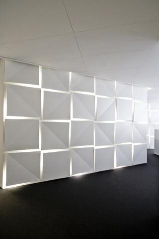Die Eingangswand mit Leucht Paneelen mit LED Hinterleuchtung. Die Wand leitet zur Empfangstheke.