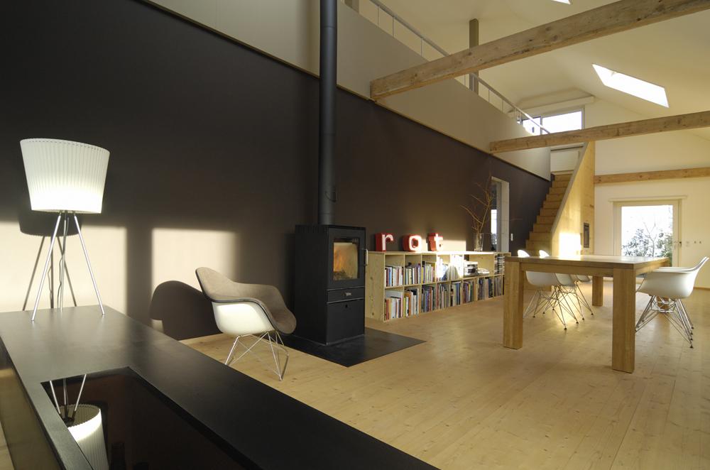 Umbau Einfamilienhaus zu einem Atelierhaus. Das Haus wurde totalsaniert und entkernt. Foto Wohnraum. Der Boden ist aus Vollholz Kiefern-Brettern, welche geölt und geseift wurden. Die lange Mittelwand wurde mit einer dunkelbraunen Le Corbusier Farbe gestrichen.