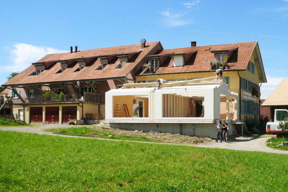 Baustellenfoto Montage Element-Holzbau auf dem bestehenden Sockel des ehemaligen Wintergartens