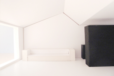 Modellfoto Innenraum mit überhohem kleinen Satteldach. Die Küche steht als hineingestellte schwarze Kiste im offenen Raum.