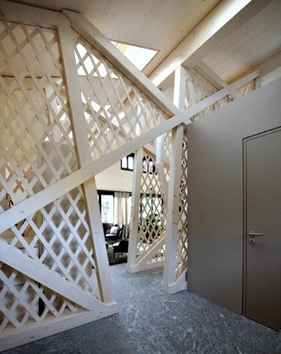 Umbau Holzhaus Ferienhaus Chalet Lenk im Simmental Berner Oberland. Der freistehende WC Kubus hinter der Holz Mittelwand. Innerhalb der Wand führt die Treppe ins Gartengeschoss.
