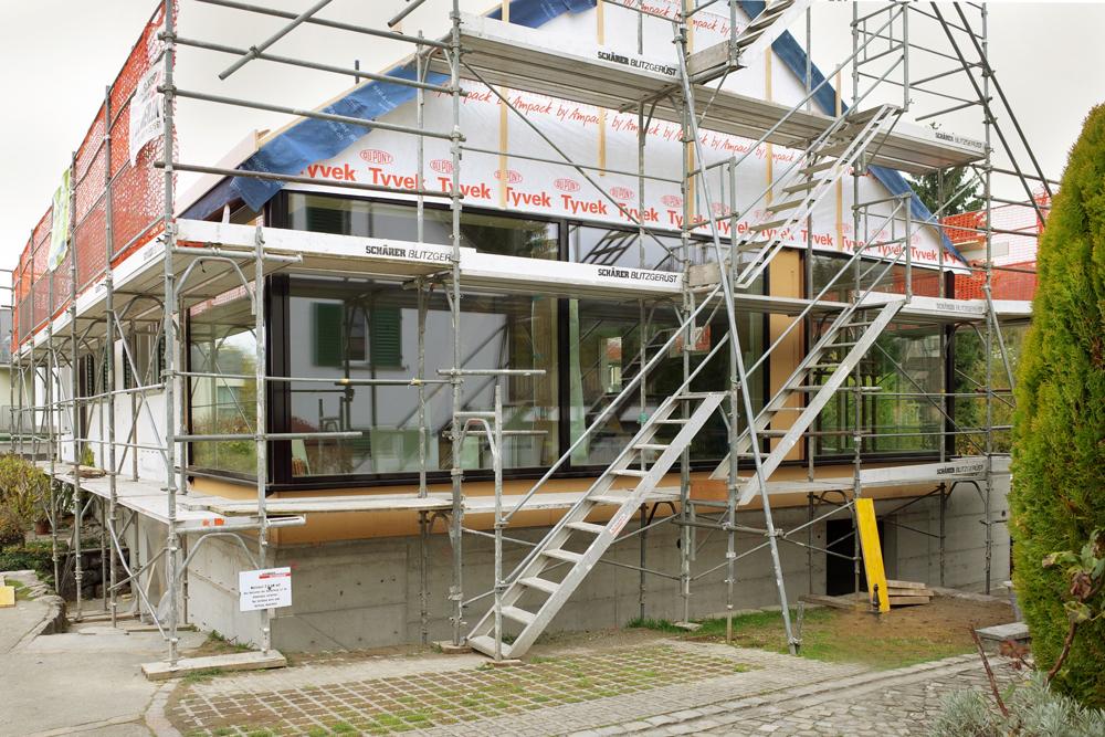 Baustellenfoto: Die neue Wohnhalle mit fertig montierter überhoher Glasfassade. Das Giebelfeld, der Betonsockel und Balkon-Ausgang werden mit schwarzem Täfer verkleidet.