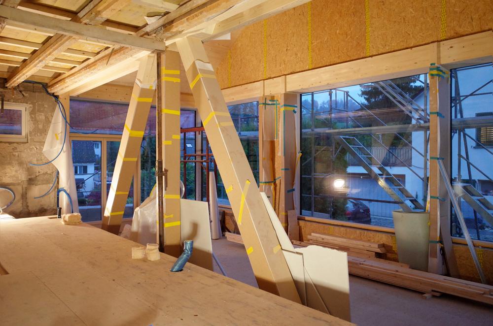 Baustellenfoto in der Morgendämmerung: Blick von der zukünftigen Küche hinab in die Wohnhalle. Die Küche wird auf dem alten 1.OG-Niveau des Altbaus stehen, die Wohnhalle ist um drei Stufen / 60cm tiefer gelegt für mehr Raumhöhe und höhere Glasfassade.