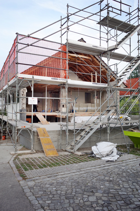 Foto Baustelle: Der Betonsockel für die neue Wohnhalle steht, die Giebelfassade ist abgebrochen. Das Gerüst ist bereits aufgestellt, der neue Holzelementbau kann kommen.