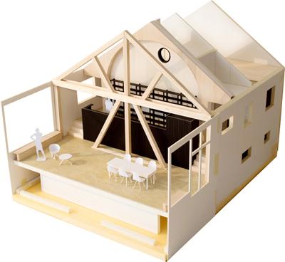 Modellfoto mit Blick auf die neue Wohnhalle. Die offene Holz-Tragkonstruktion steht da, wo vorher die Giebelfassade des alten Hauses stand. Hinter der Holz-Tragkonstruktion die Küche mit Bogenwand aus Holz.