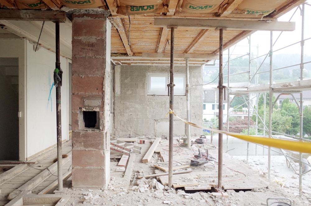 Foto Baustelle nach Abbruch der Giebelfassade. Wo das gelbe Band verläuft, wird später die neue Küche stehen, von welche aus man in die neue Wohnhalle und hinaus in die Landschaft blicken wird.