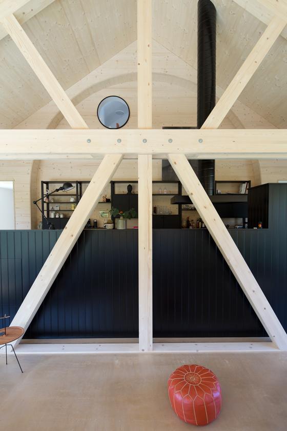 Die Hausverlängerung ist ein Holzbau mit Tragwerk und Bogenwand. Die Bogenwand haben wir entworfen, weil uns das dreieckige Giebelfeld als Raumabschluss zu agressiv und uninspiriert erschien. Der Wandbogen harmonisiert das Ganze. Der Wandbogen ist eine Referenz an alte Markthallen und gibt der Küche eine sehr starke Verankerung und Identität im Raum. Oben unter dem Bogen schwebt ein Bullauge, dahinter befindet sich die Dusche des Dachgeschosses. Man hat aus der Dusche einen wunderbaren Ausblick in die Wohnhalle hinunter. Obwohl die Wohnhalle ein hoher Raum ist, kommt sie ganz ohne Dachfenster aus und ist auch an Regentagen dank der überhohen Glasfassade taghell belichtet. Die Dachuntersicht ohne Dachfenster oder sonstige Unterbrüche strahlt eine erhabene Ruhe aus. Der Boden ist ein ungefärbter geölter Anhydrith. /// Umbau und Erweiterung 40er Jahre Haus Meilen, nijo architekten Zürich, Nina und Johannes Wick