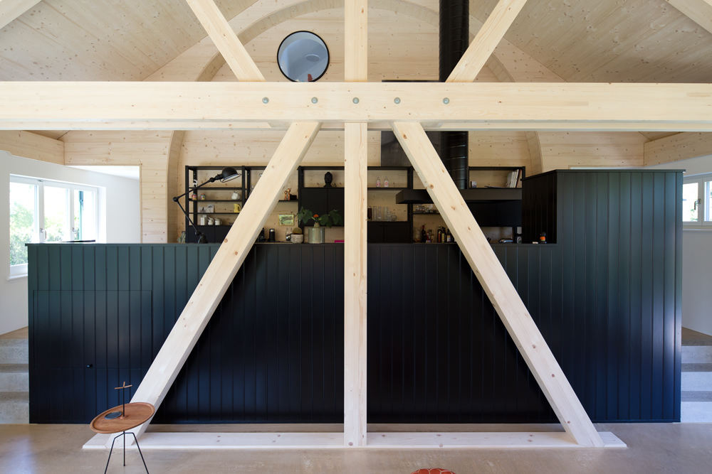 Das Holztragwerk steht an der Stelle, wo sich früher die östliche Giebelfassade befand. Unter dem Tragwerk befindet sich die alte Keller-Aussenwand, man konnte daher auf eine Fundation verzichten. Die schwarze Küchenzeile steht drei Stufen erhöht auf dem Altbau-Boden. Die schwarze Täferung ist mit Ölfarbe gestrichen. Der raumhohe Wandbogen bildet den Abschluss der Küche und bietet Platz für das schwarze Küchenregal. Hinter dem Bullauge oben unter dem Dach befindet sich die Dusche. /// Umbau und Erweiterung 40er Jahre Haus Meilen, nijo architekten Zürich, Nina und Johannes Wick