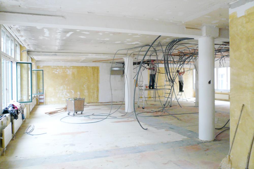 Baustellenfoto fertig ausgeräumte Etage. Die Tragstruktur kommt zum Vorschein: zwei runde Stahlstützen mit von Fassade zu Fassade verlaufenden Stahlträgern.