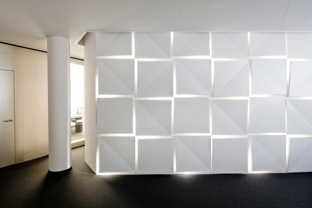 Eingang Empfang mit hinterleuchteter LED Kachelwand. Die Bürotrennwand ist in Champagnergold lasiert.