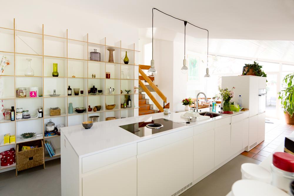 Die neue Küche steht als freistehendes Element im Raum. Es ist keine Kochinsel, eher eine verbreiterte freistehende Längszeile. Die Küche wurde so platziert, dass man beim Kochen in den Wohnraum blicken kann und nie mit dem Rücken zu den Gästen steht.
