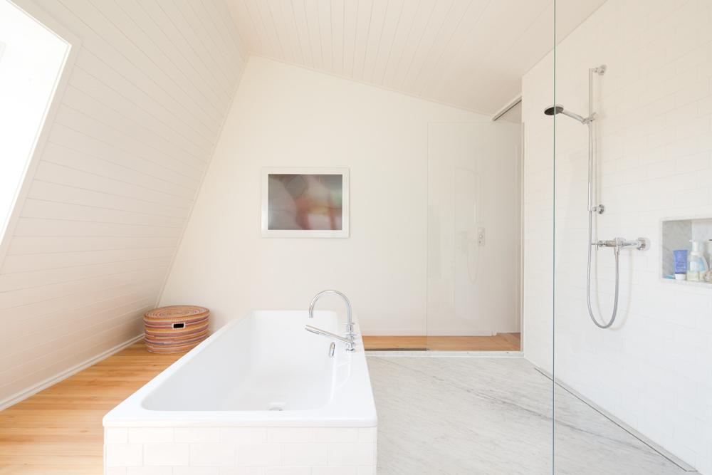 Das Bad wurde in ein Dachzimmer verlegt. Das ursprüngliche, sehr kleine 60er Jahre Badezimmer wurde zur Ankleide umfunktioniert. Im neuen Bad bildet die offene Dusche mit Carrara-Marmor-Boden und freistehender Badewanne den Mittelpunkt. Den originalen Holzbretterboden haben wir belassen damit ein möglichst wohnliches Bad entsteht.