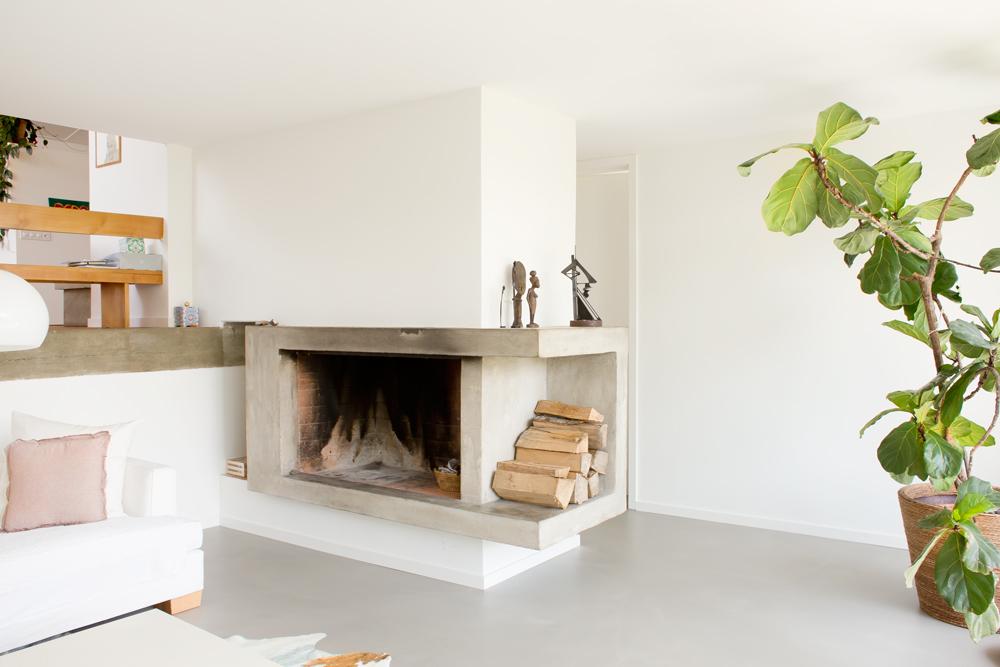 Das Wohnzimmer liegt in der unteren Ebene mit direktem Zugang zum Garten und südseitiger Vollverglasung. Über die offene Geschosskante sieht man in die mittlere Eingangsebene mit Küche und Essplatz. Die hölzerne Absturzsicherung ist gleichzeitig auch eine Sitzbank. /// Umbau 60er Jahre Haus Split-Level Watt Regensdorf nijo architekten Zürich