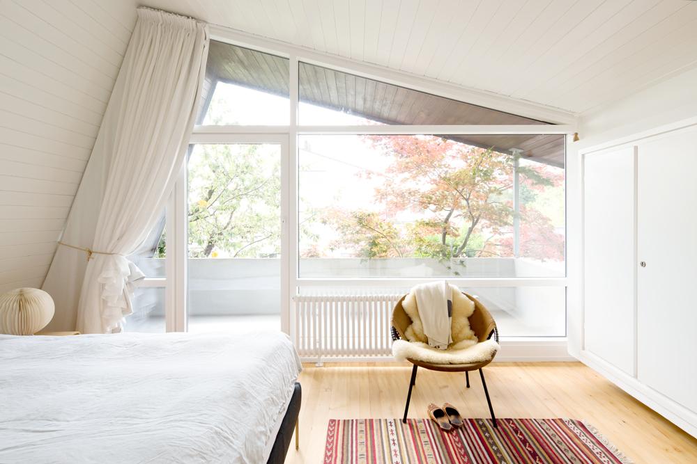 """Das Schlafzimmer befindet sich in der obersten Ebene und verfügt über eine seitliche Glasfassade mit kleinem Balkon. Der Einbauschrank ist durch die Wand """"durchgesteckt"""" und tritt über dem Essplatz als weisser Kubus in Erscheinung. /// Umbau 60er Jahre Haus Split-Level Watt Regensdorf nijo architekten Zürich Nina und Johannes Wick"""