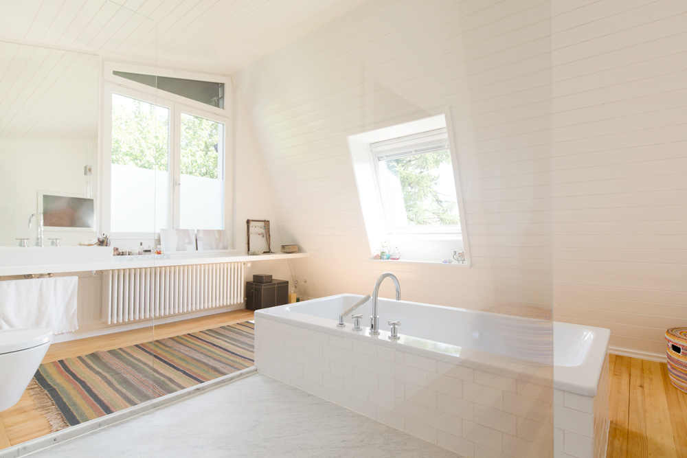 Die Marmor-Dusche und die geplättelte / geflieste Badewanne bilden ein freistehendes Element im Raum. Wir haben diesen Weg gewählt, weil dieser Raum ursprünglich ein normales Zimmer war und wir den Raum nicht allzufest wie ein herkömmlicher Nassraum ausstaffieren wollten. Das Lavabo steht auf dem verbreiterten Fenstersims, seitlich an das Fenster schliesst der grossflächige Spiegel an../// Umbau 60er Jahre Haus Split-Level Watt Regensdorf nijo architekten Zürich