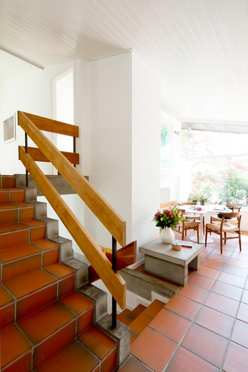 Die zentrale offene Treppe verbindet die Halbgeschosse (Split-Level). Die Treppe bildet mit dem Betoncheminee im Wohnzimmer und dem massiven Kamin eine Einheit. Das Haus ist in den 60er Jahren sehr detailreich mit Sichtbeton-Abschlüssen gekonnt ausgeführt worden. /// Umbau 60er Jahre Haus Split-Level Watt Regensdorf nijo architekten Zürich Nina und Johannes Wick