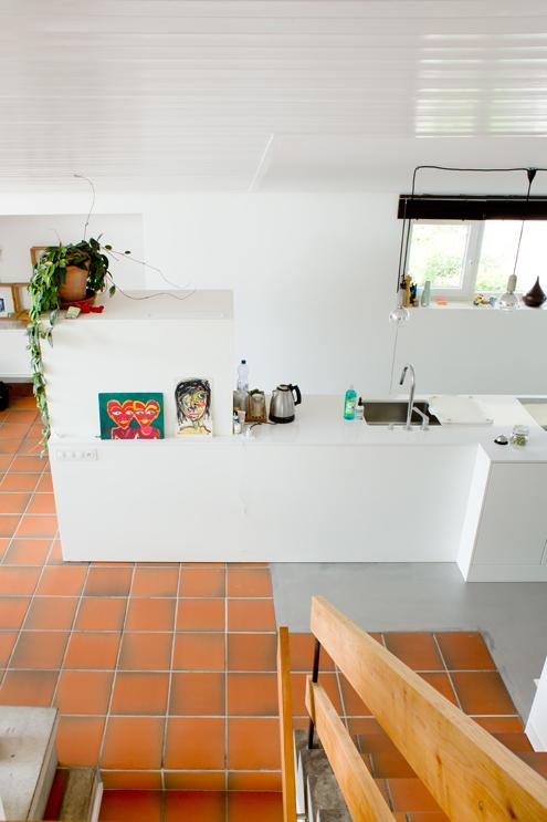 Blick von der oberen Etage auf die mittlere Eingangsetage mit der neuen Küche. Am Verlauf des Tonplattenbodens und dem Verlauf der Deckentäferung erkennt man die ehemalige Raumteilung mit der abgeschlossenen dunklen Küche. Die neue Küche überlagert diese Material- und Raumschichten bewusst und macht ein neues Ganzes aus dem Raum. /// Umbau 60er Jahre Haus Split-Level Watt Regensdorf nijo architekten Zürich