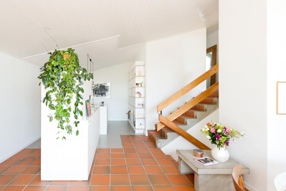 Die mittlere Eingangsebene mit der neuen geöffneten Küche. Die Küchenzeile steht frei im Raum und dient als verbindendes Element zwischen den verschiedenen Raumzonen. An Boden und Decke ist der Materialwechsel gut ablesbar: Hier war früher die Trennwand zur abgeschlossenen Küche. Der originale Tonplattenboden wurde im hinteren Küchenbereich mit einem Gussboden ergänzt. /// Umbau 60er Jahre Haus Split-Level Watt Regensdorf nijo architekten Zürich Nina und Johannes Wick