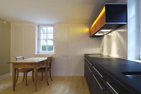 Die neue Küche im ehemaligen Stall. Die Küche ist als schwarzer Kubus in den Raum hineingestellt und übernimmt auch die Belichtung des Raumes.
