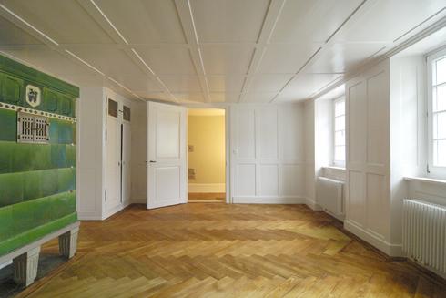 Das Wohnzimmer mit altem Kachelofen und Fischgratparkett in Eiche. Der Parkett wurde saniert und faule Stellen ergänzt.